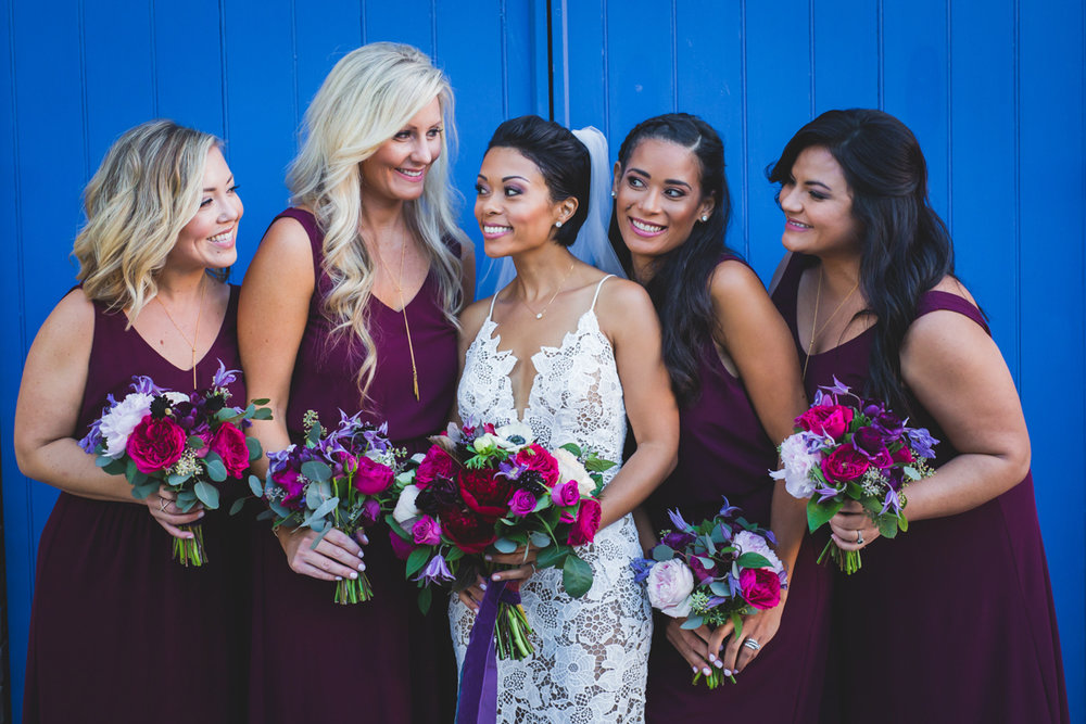 New Orleans Destination Wedding bride and bridesmaids in front of bright wall