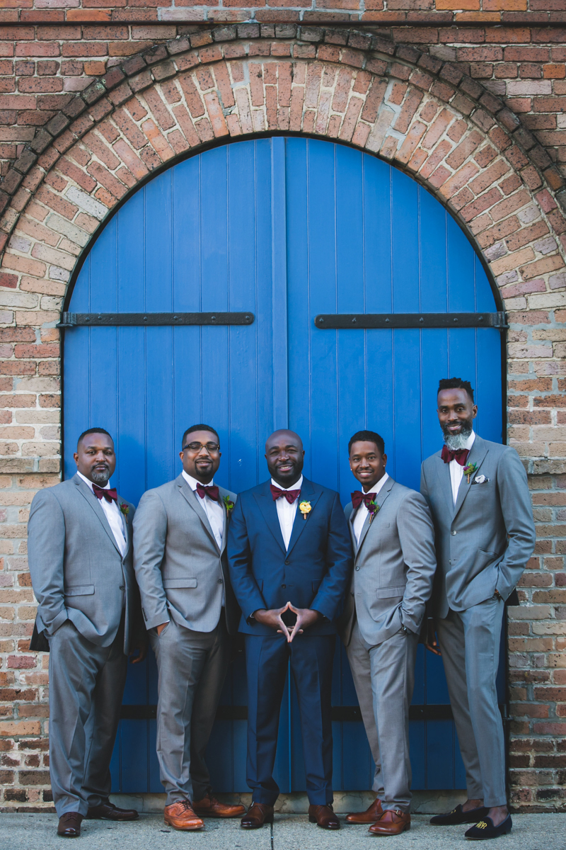 New Orleans Destination Wedding groom with groomsmen in front of arch door