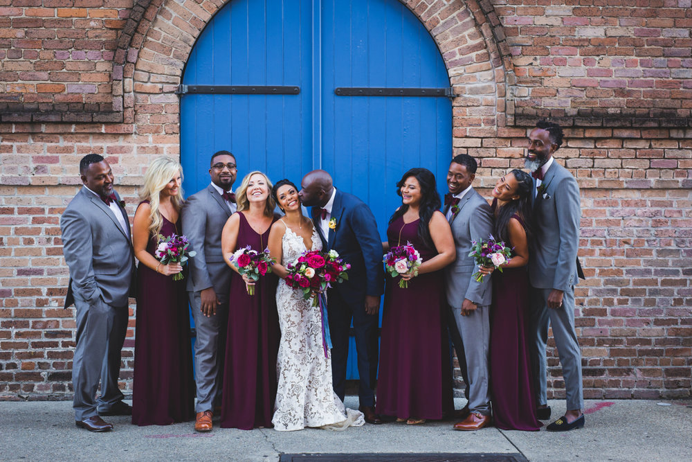 New Orleans Destination Wedding wedding party in front of arch door and brick