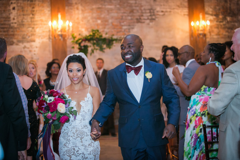 New Orleans Destination Wedding bride and groom holding hands down aisle while guests clap