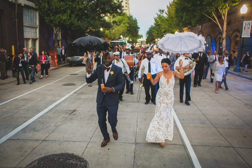 New Orleans Destination Wedding newly married couple leading second line parade holding drinks and feathery umbrellas