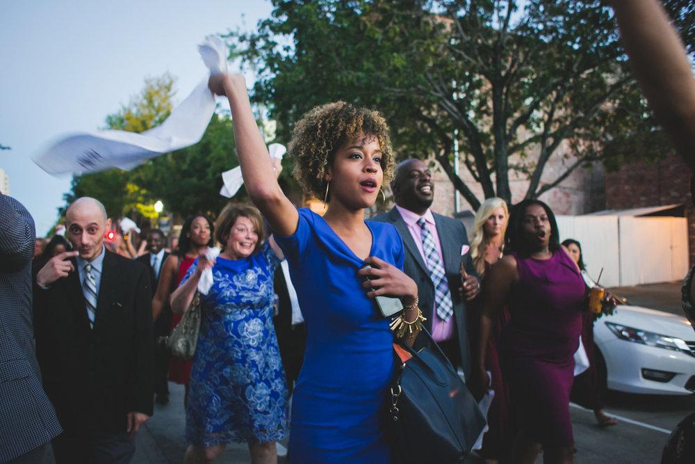 New Orleans Destination Wedding guest waving silkscreen handkerchief during parade