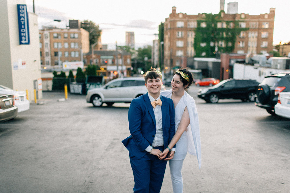 newlywed couple holding hands and smiling in parking lot after wedding in suit and bowtie and white jumpsuit with cape fuck yeah weddings seattle washington