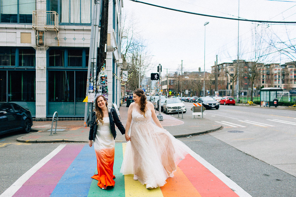 andrea and leigh smiling and holding hands in their wedding dresses and motorcycle jacket while walking across rainbow crosswalk seattle washington fuck yeah weddings seattle washington