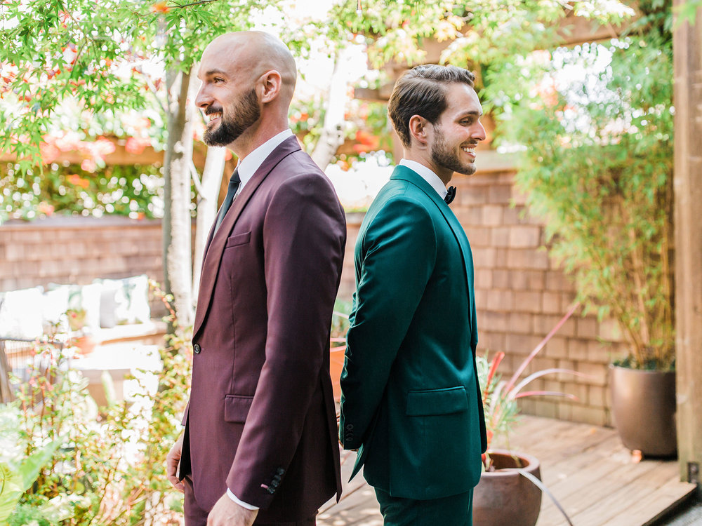 two grooms in velour suits standing back to back in garden at wedding Apollo Fotografie San Francisco