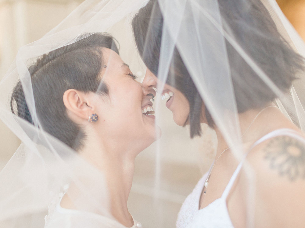 two brides about to kiss under veil at wedding Apollo Fotografie San Francisco