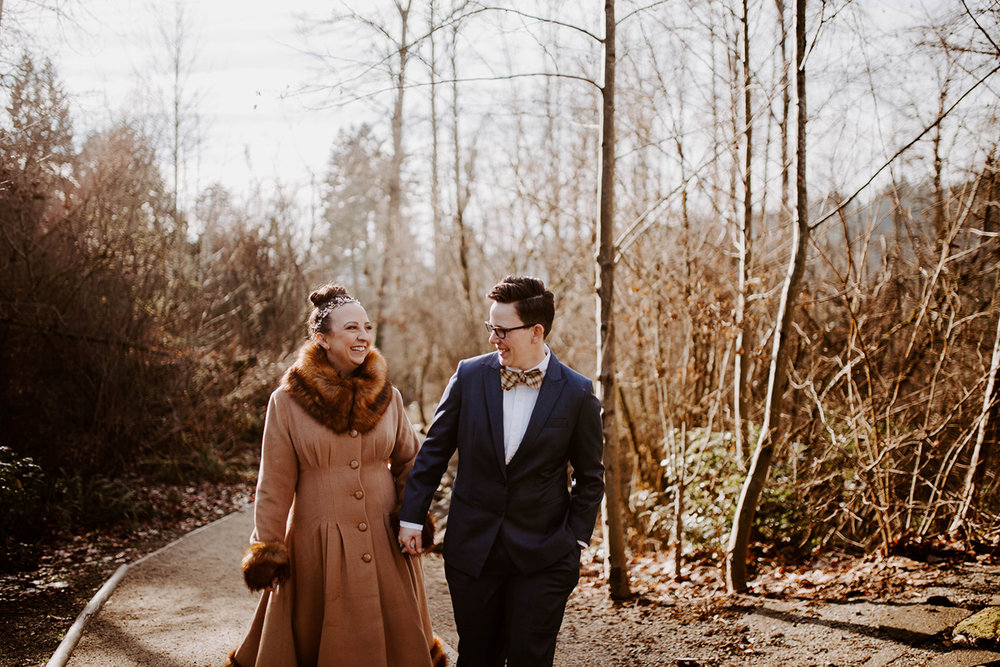queer surprise home wedding couple walking down path through woods