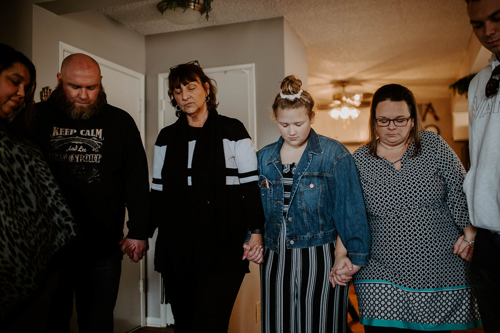 queer surprise home wedding guests holding hands during prayer circle