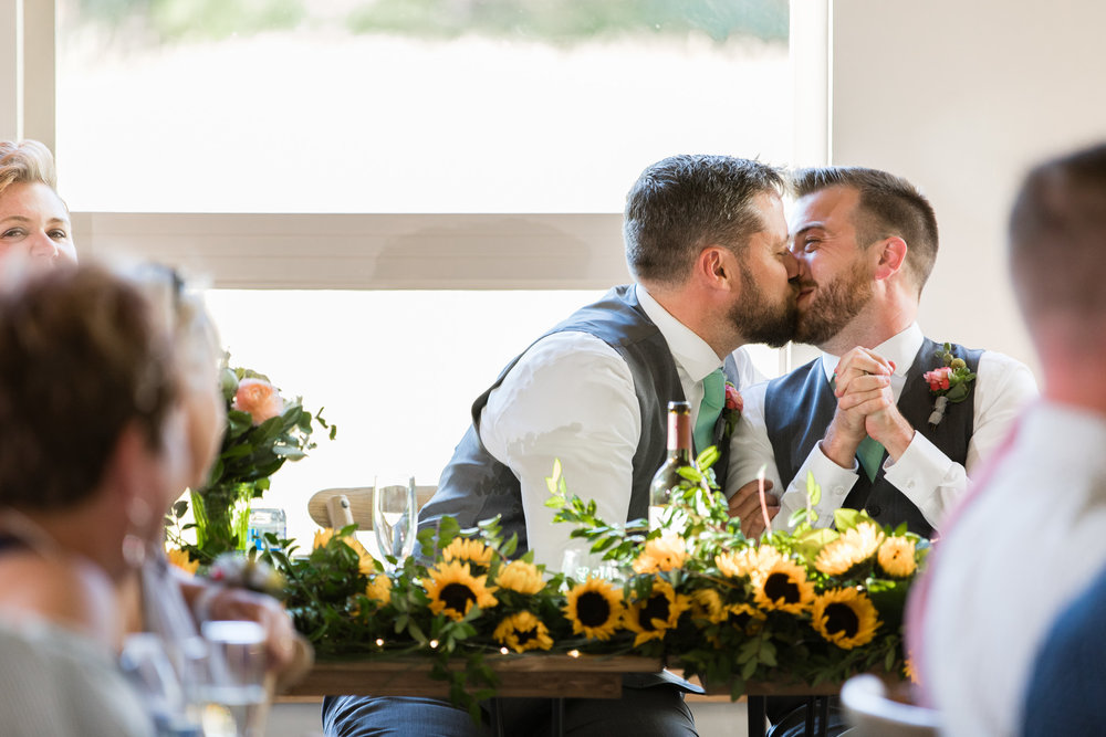 two grooms sharing a kiss at the head table during their wedding reception with sunflowers on the table Meera Graham Photography Missoula Montana