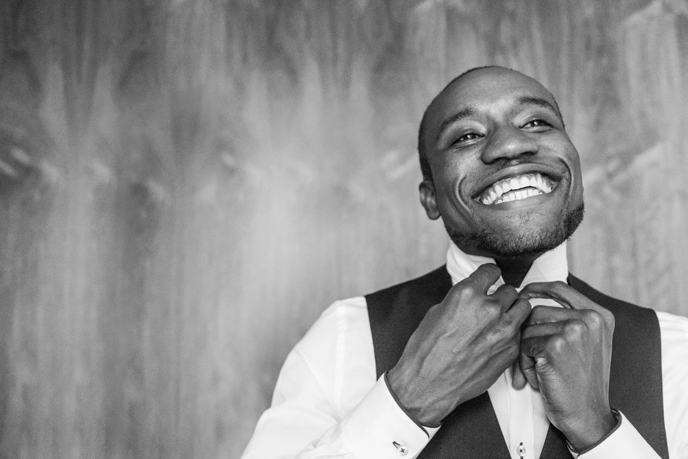 groom smiling wide and adjusting his collar and tie before his wedding ceremony Meera Graham Photography Missoula Montana