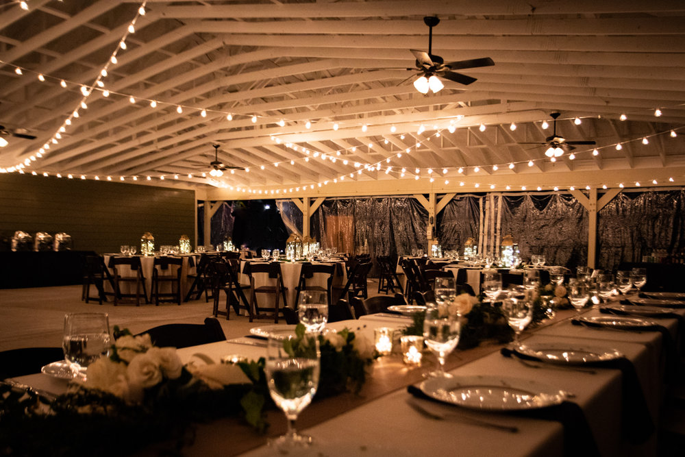 Romantic, Intimate-Feeling Wedding reception venue with tables and white lights hanging from high rafters