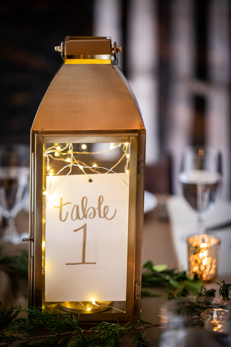 """Romantic, Intimate-Feeling Wedding lantern filled with string lights reading """"table 1"""""""