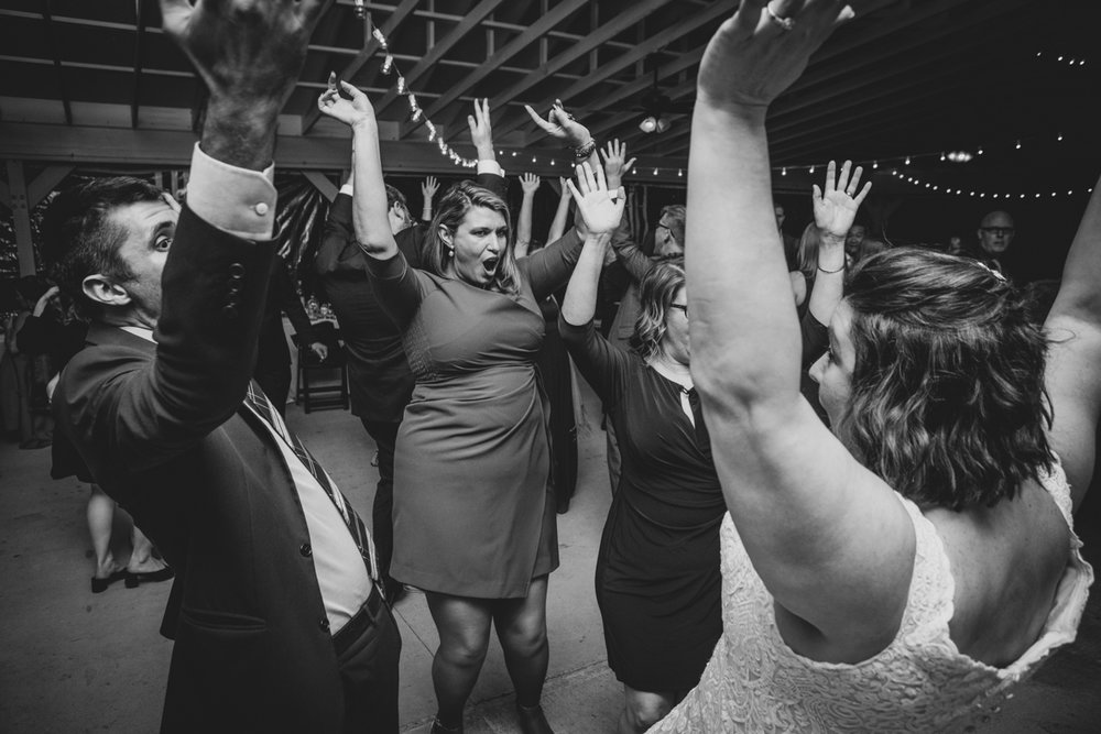 Romantic, Intimate-Feeling Wedding bride and guests on dance floor with arms in the air