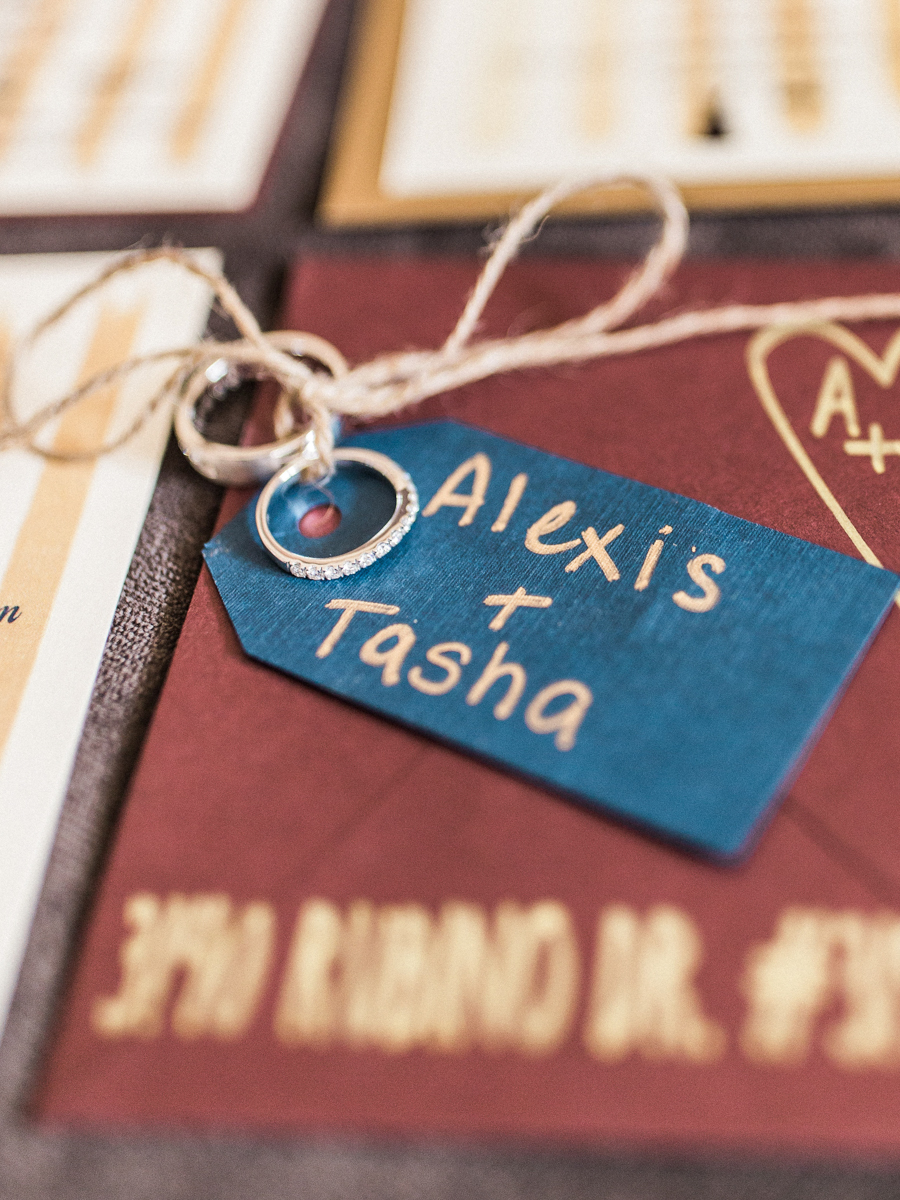 """los altos lutheran same-sex wedding tag reading """"alexis + tasha"""" with engagement rings tied to it with twine"""
