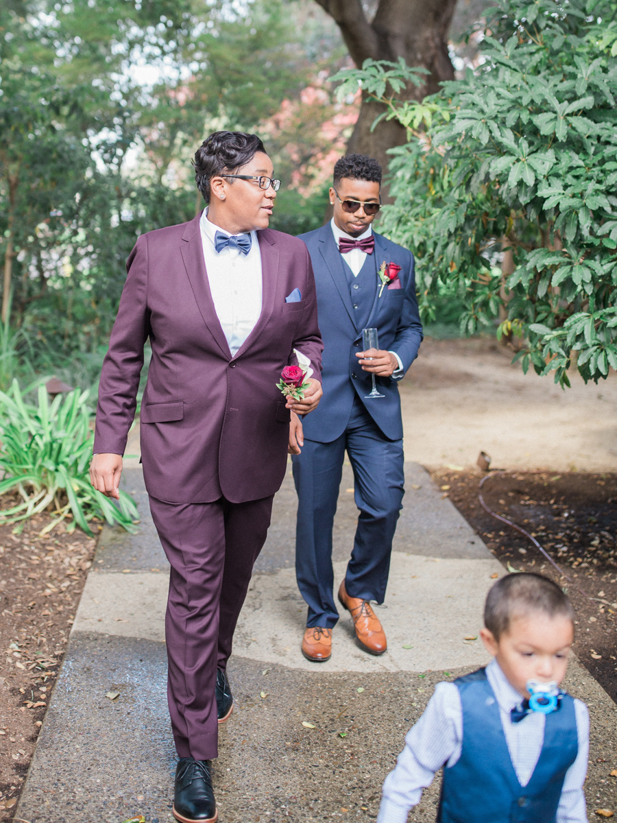 los altos lutheran same-sex wedding alexis, member of wedding party, and child walking down path