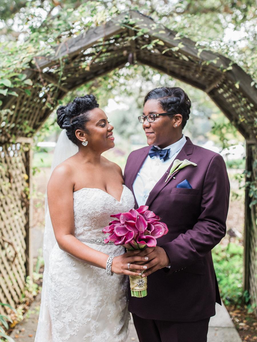 los altos lutheran same-sex wedding couple holding bouquet between them under garden trellis