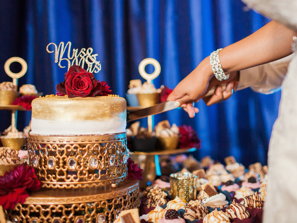 """los altos lutheran same-sex wedding couple cutting cake topped with roses and gold cake topper reading """"mrs. and mrs."""""""