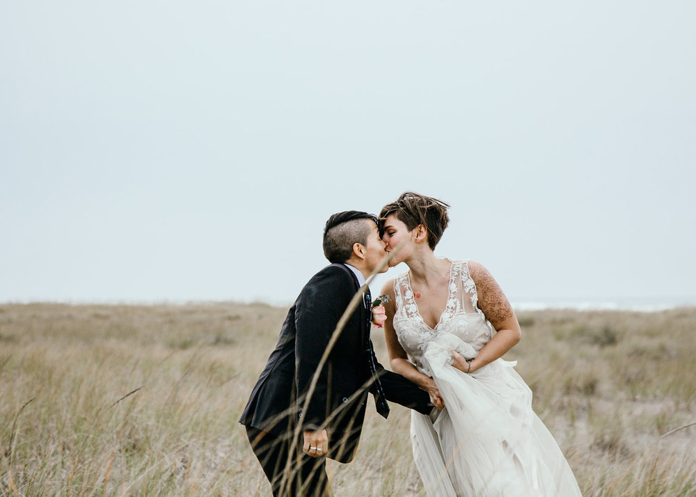 Karla and Mary lean in to share a kiss in the tall grass of the beach at Oregon seaside wedding shoot by Austin Texas LGBTQ friendly photographer Ziggy Shoots