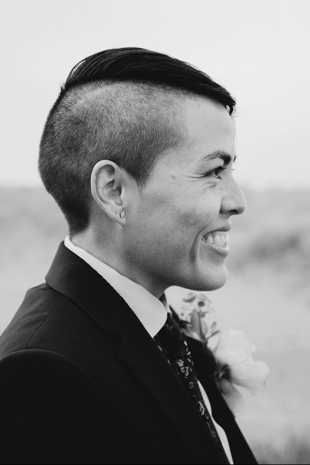 Karla in suit smiling wide while looking at Mary at wedding on the Oregon seaside by Austin Texas LGBTQ friendly photographer Ziggy Shoots