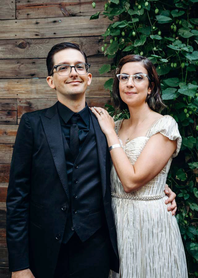 newlywed couple posed together in vintage rockabilly attire in front of green wall by Austin Texas LGBTQ friendly photographer Ziggy Shoots