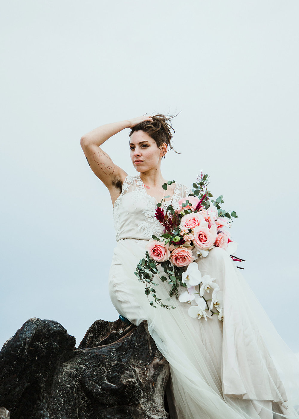 Mary in wedding dress with bouquet sitting on rocks on the Oregon shore and showing off tattoos and armpit hair by Austin Texas LGBTQ friendly photographer Ziggy Shoots