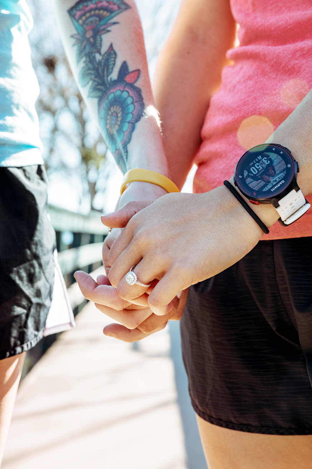 tattooed engaged couple holding hands and showing off engagement rings on a sunny pathway by Austin Texas LGBTQ friendly wedding photographer Ziggy Shoots
