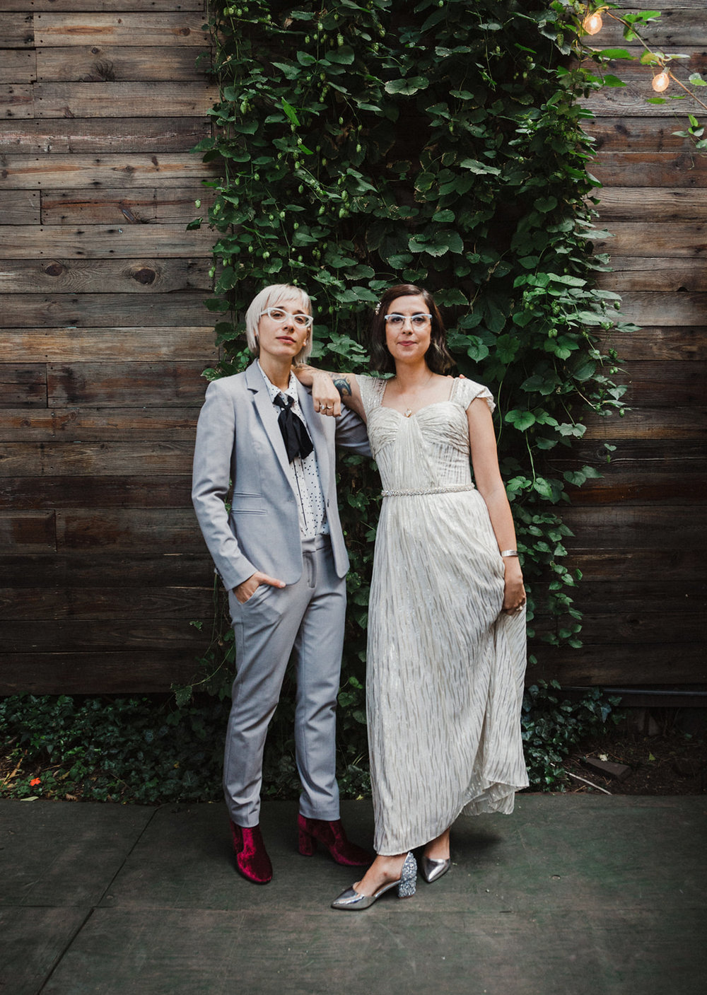 bride in vintage glam and guest in gray suit getting portrait in front of green wall by Austin Texas LGBTQ friendly photographer Ziggy Shoots