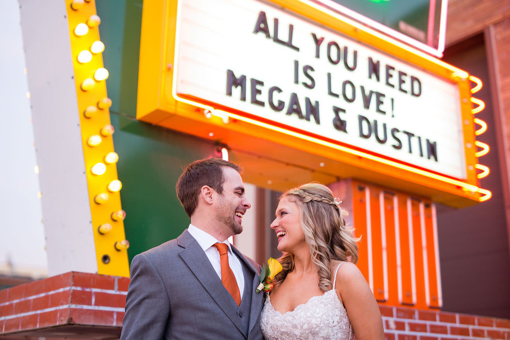 """Dustin and Megan in from of a marquee sign that reads """"All You Need is Love!"""" at the American Sign Museum in Cincinnati"""