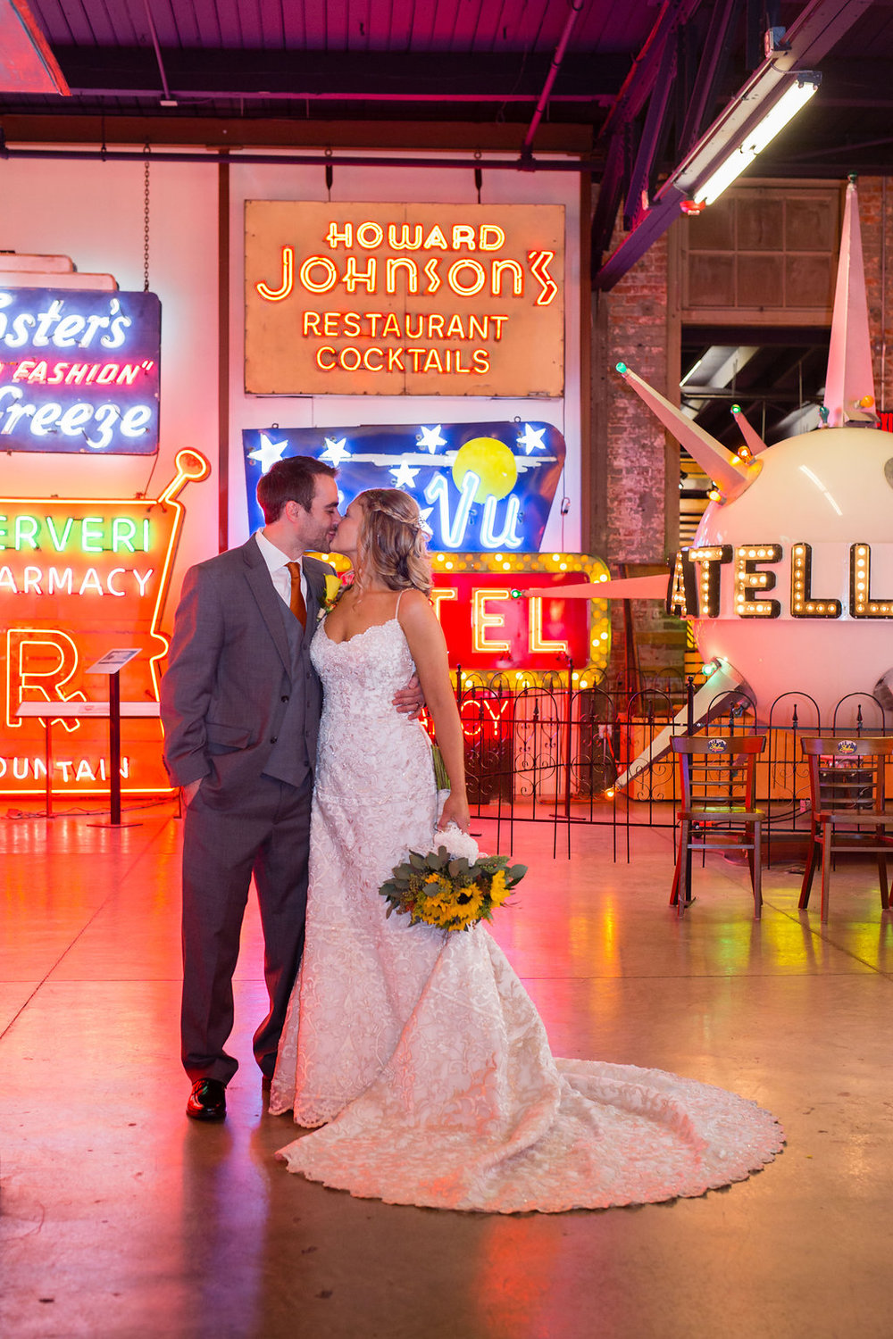 Megan and Dustin kiss in front of the neon signs at the American Sign Museum in Cincinnati