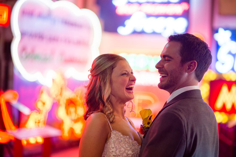 Megan and Dustin smiling at their wedding in front of the neon signs at the American Sign Museum in Cincinnati Ohio