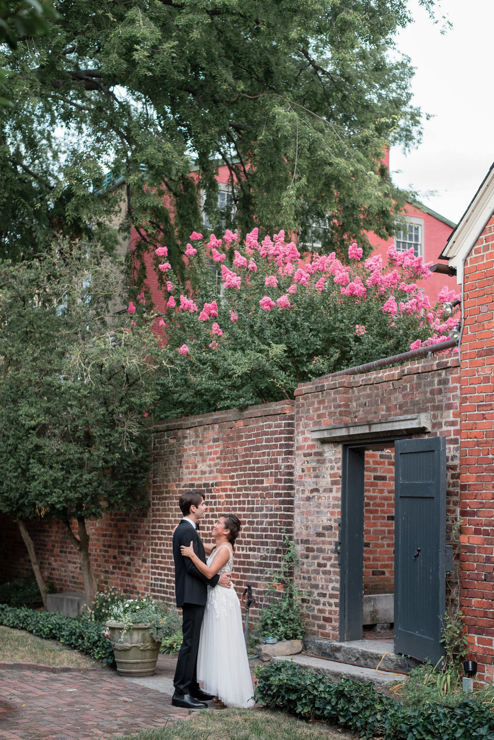 Ben and Christina in suit and white lace wedding dress outside garden gate at Poe Museum in Richmond Virginia