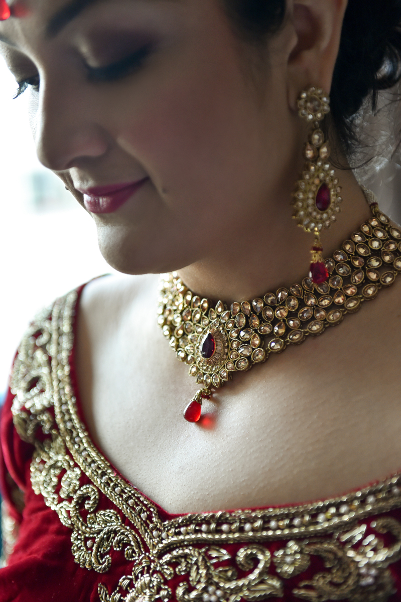 Mita dressed for the Indian wedding ceremony in her gold and red necklace, earrings and sari