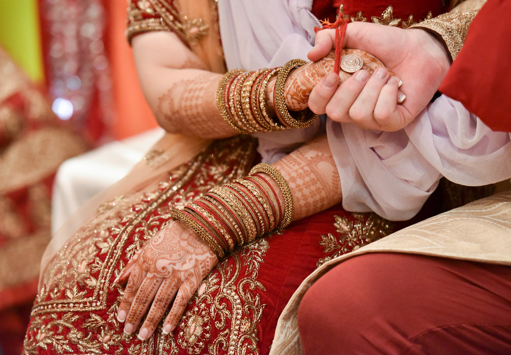 Mita and James seated and holding hands as part of their Indian wedding ceremony in Hong Kong