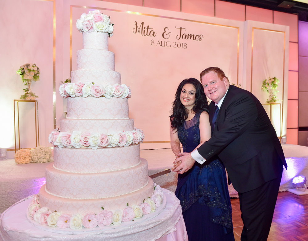 Mita and Jame cutting their large 8-tier wedding cake at their wedding reception in Hong Kong