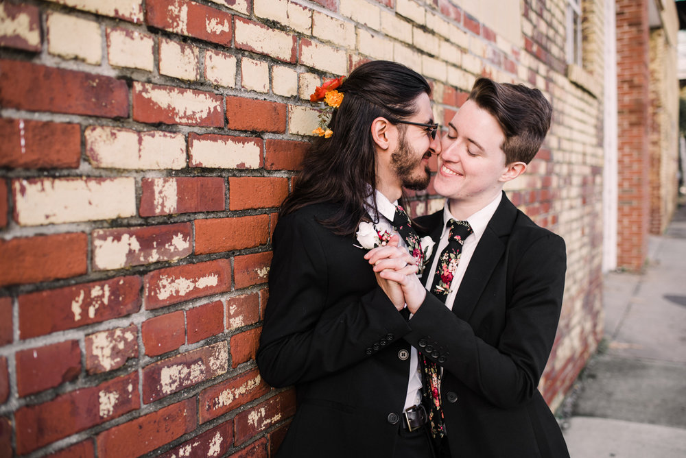 intimate wedding richmond virginia embrace holding hands and leaning against wall