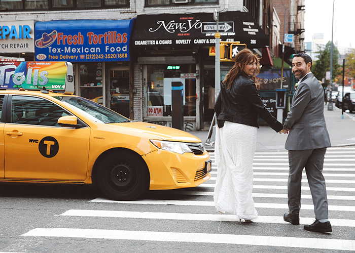 newlywed couple holding hands walking across street in new york city