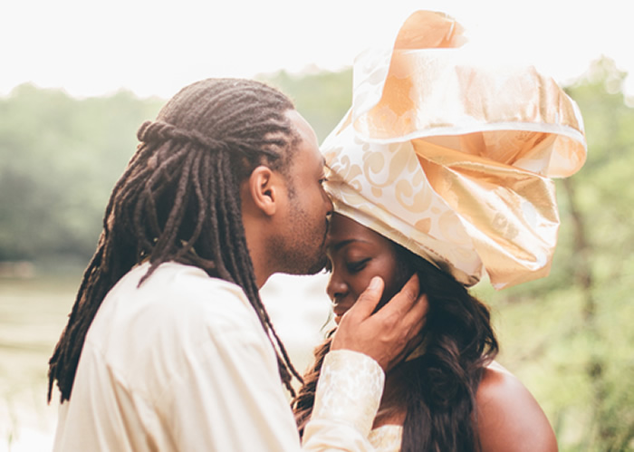 groom kissing bride on forehead at engagement session