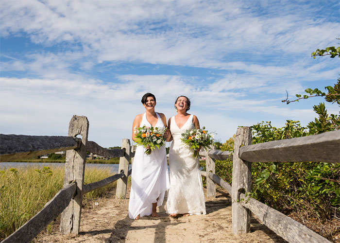 two brides walking on sandy path at beach boston massachusetts