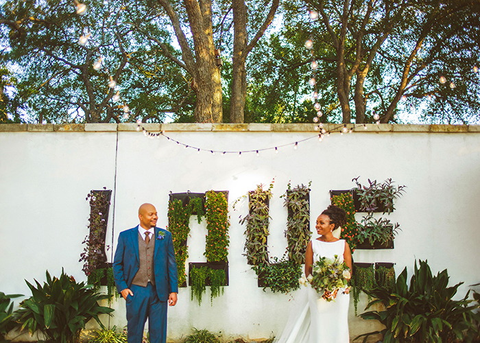 newlywed couple standing on either say of LOVE greenery wall napa valley california
