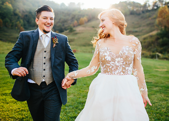 couple running through field holding hands after wedding