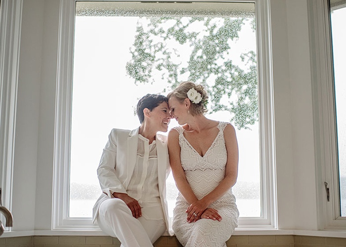two brides kiss in window after wedding