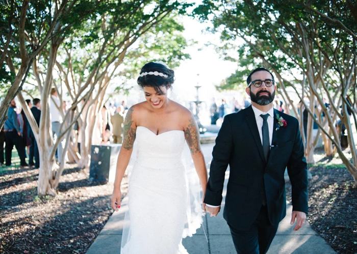 newlywed bride and groom walking down path in suite and wedding dress richmond virginia
