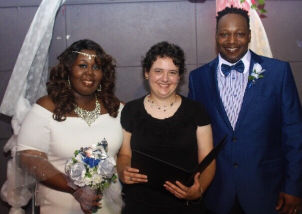 Carly Miller standing with newlywed couple in Durham North Carolina