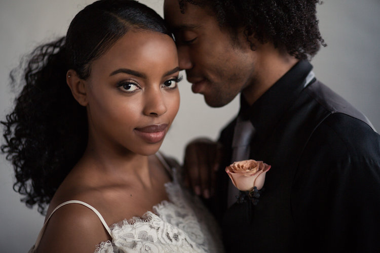 black bride and groom nuzzling foreheads after wedding