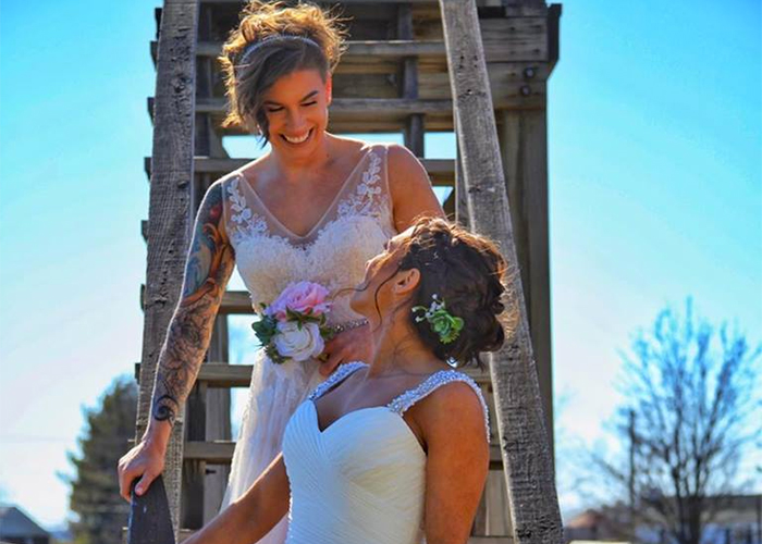 two newlywed brides smiling at each other on ladder Texas