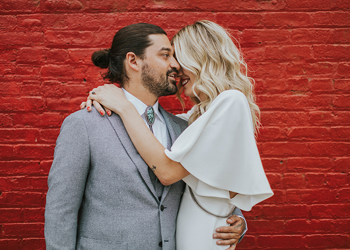 newlywed couple snuggle up in front of red brick wall new york city