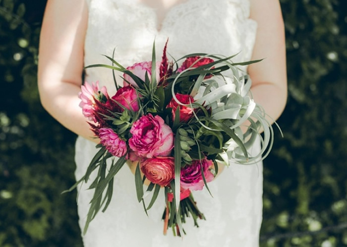 bride holding bouquet of roses and succulents