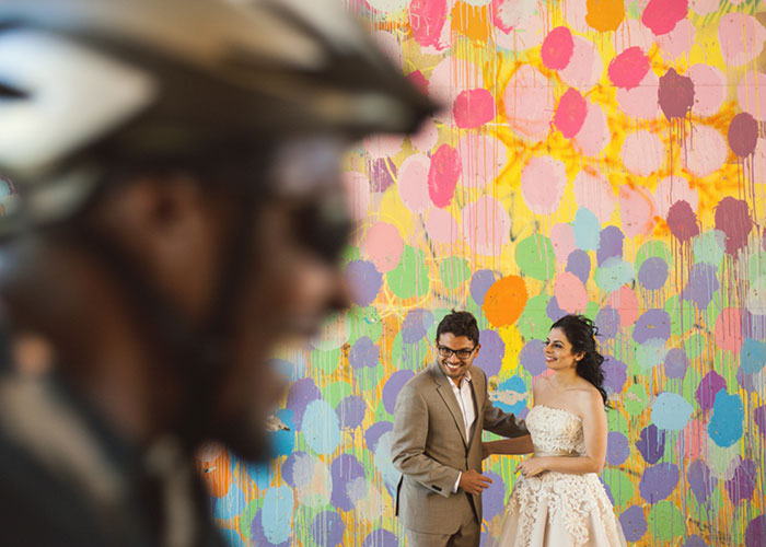 newlywed couple against mural wall as biker rides past altanta georga