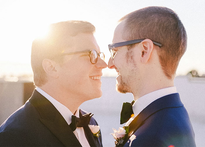 two grooms touch noses at wedding philadelphia pennsylvania