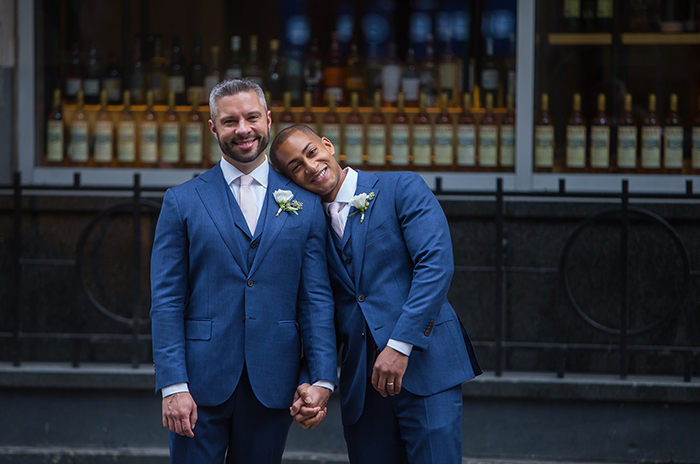 two grooms holding hands in matching suits after their wedding new york city